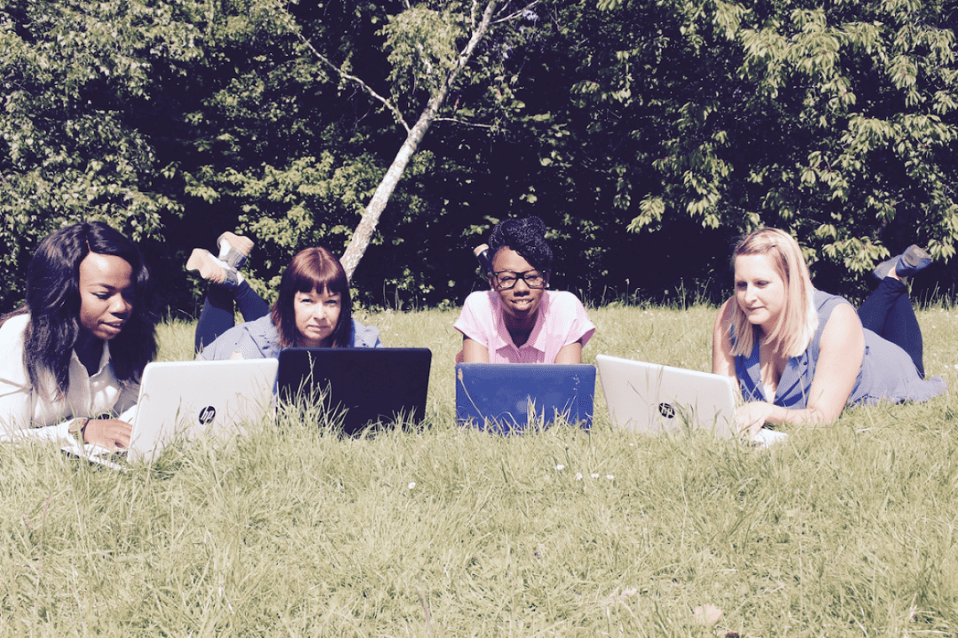4 ladies lying in the grass with their laptops